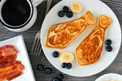 Fathers Day tie shaped pancake breakfast, above view table scene on a dark wood background. Tie shaped pancakes with blueberries and bananas. Fathers Day royalty free stock photos