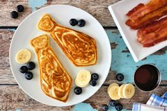 Fathers Day tie shaped pancake breakfast, top view table scene on rustic blue wood. Tie shaped pancakes with blueberries and bananas. Fathers Day breakfast stock images