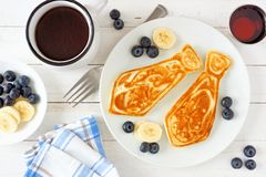 Fathers Day tie shaped pancake breakfast, top view table scene on white wood. Tie shaped pancakes with blueberries and bananas. Fathers Day brunch concept. Top stock images