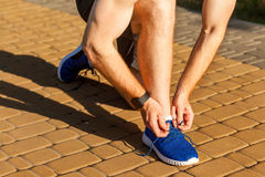 Tie shoelaces. Blue sneakers. Runnig Stock Photography