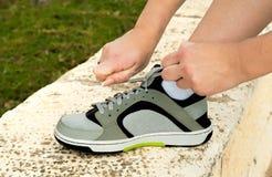 Tie shoelaces on sneakers. Athlete runner tying shoelaces on sneakers before the competition Royalty Free Stock Photo