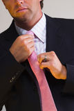 Tie and suit. A handsome man sets right his trendy tie stock photos