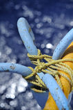 Tied Anchor. A view of a blue anchor tired with ropes on a ship railing, on the backdrop of shiny blue sea water Royalty Free Stock Photo