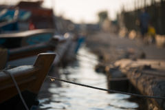 Tied boats at fishing shelter. Focus is on the rope Stock Images