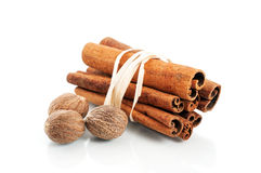 Tied cinnamon sticks and nutmeg over white Stock Photo