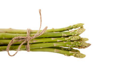 Tied fresh raw asparagus. On white background Royalty Free Stock Images