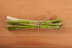 Tied fresh raw asparagus. On wooden background Royalty Free Stock Image