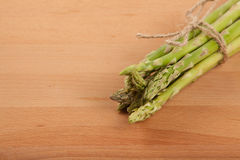 Tied fresh raw asparagus. On wooden background Stock Photography