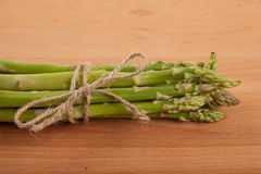 Tied fresh raw asparagus. On wooden background Royalty Free Stock Images