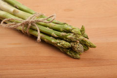 Tied fresh raw asparagus. On wooden background Stock Photos
