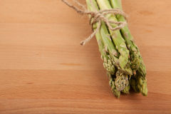 Tied fresh raw asparagus. On wooden background Stock Image