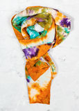 Tied hand painted silk scarf on concrete Royalty Free Stock Images