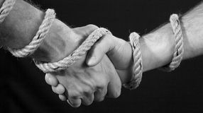 Tied handshake. Man's handshake tied with a boat-rope Royalty Free Stock Photos