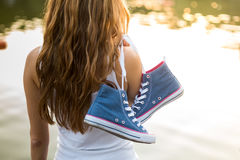 Tied pair of sneakers hanging on a girl Royalty Free Stock Photos