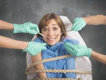 Tied to the dentist. Girl tied to a chair at dentist Royalty Free Stock Photo
