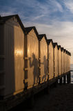 Tied togheter. A row of cabins at the beach tied together with the shadow of the two girls holding their hands Stock Photos