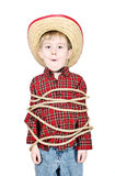 Tied up. A young boy dressed up in a cowboy costume is tied up with rope Royalty Free Stock Image