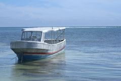 Tied up boat looking out toward the sea. Small boat tied to the shoreline Stock Photography