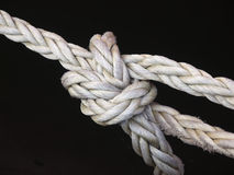 Tied Up in Knots. Closeup of white nylon rope tied in a knot against a black background stock images