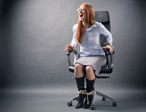 Tied Up Woman - No Freedom in Business. A young businesswoman confined to an office chair shouting for help and trying to free herself Royalty Free Stock Photos