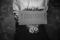 Tied weak victim showing a sign with a ransom sum Stock Images