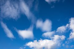 Tiefe blaue Himmel u. flaumige Wolken Stockbilder