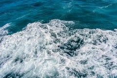Tiefe blaue stürmische Meerwasseroberfläche mit weißem Schaum- und Wellenmuster Stockbild