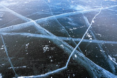 Tiefe breite Sprünge im dunkelblauen gefrorenen Wasser der Bucht Lizenzfreies Stockfoto