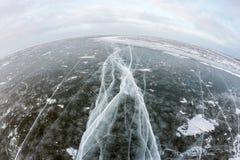 Tiefe breite Sprünge im dunklen gefrorenen Wasser in fisheye Vision Stockfoto