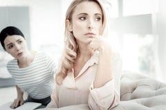 Tiefe unglückliche Frau, die beiseite schaut, berührend zu ihrem Kinn Lizenzfreie Stockbilder