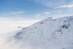 Tiefe Wolken schlägt die schneebedeckte Bergspitze im Tatras ein lizenzfreie stockfotos