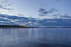 Tiefer bewölkter Marine-Blau-schwerer Sonnenuntergang-Himmel mit rote Licht-Überwasserlandschaft lizenzfreie stockfotografie