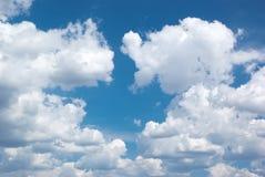 Tiefer blauer Himmel und große Wolken stockbild