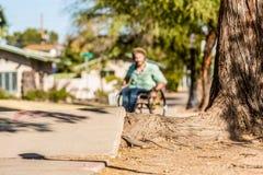 Tiefer Fokus-Mann im Rollstuhl stellt Bürgersteigs-Hindernis gegenüber Stockbilder