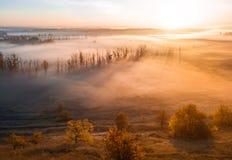 Tiefer starker Nebel im Tal Lange Schatten von den Bäumen Atmosphärische schöne Dämmerung Luftbrummenfoto Überraschen lizenzfreie stockfotos
