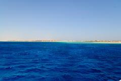 Tiefes blaues Meer mit gelber Küstenlinie Stockbild