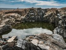 Tiefes Gezeiten-Pool in der rosa Granit-Küstenlinie, Schoodic-Punkt, Acadia-Nationalpark Lizenzfreies Stockfoto
