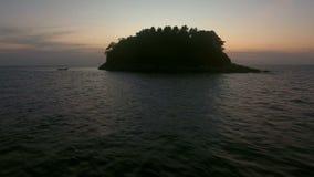 Tiefflug über Fischerboot nahe wilder Insel mit Sonnenuntergangansicht stock video footage
