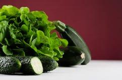 Tiefgrünes unterschiedliches Gemüse auf reichem marsala Hintergrund, Nahaufnahme lizenzfreie stockfotografie