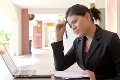 Tiefstand und Tempus der jungen asiatischen Geschäftsfrau stockfoto