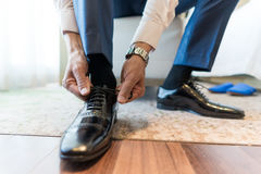 Tieing Shoe. The groom bent over to tie his shoe Royalty Free Stock Photography