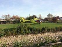 TIEL holandie - LISTOPAD 14, 2018: Żółty medyczny helikopter lądujący pomagać w pomocy medycznej w obszarze zamieszkałym obraz stock