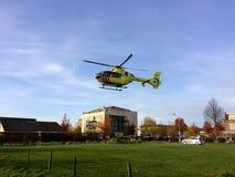 TIEL holandie - LISTOPAD 14, 2018: Żółty medyczny helikopter zdejmuje po pomagać w pomocy medycznej w obszarze zamieszkałym obraz royalty free
