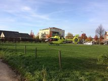 TIEL, THE NETHERLANDS - NOVEMBER 14, 2018: Yellow medical helicopter assisting in medical aid in residential area. In the Netherlands. Landed in a green pasture royalty free stock images