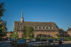 Brick building and parking lot at sunset in Tielt. Tielt, Belgium - July 02, 2017. Brick building and parking lot at sunset in Tielt. Charming and quiet village Royalty Free Stock Image
