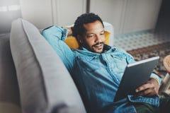 Tiempo africano barbudo joven de la frialdad del gasto del hombre en sofá y mirada del apartamento moderno de la tableta Concepto Imagen de archivo
