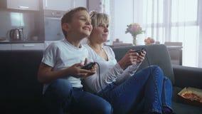 Tiempo alegre del gasto de la familia que juega al videojuego almacen de metraje de vídeo