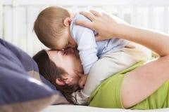 Tiempo armonioso: Madre e hijo que abrazan con amor y tenderne Foto de archivo