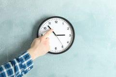Tiempo cambiante del hombre en el reloj de pared hermoso fotos de archivo