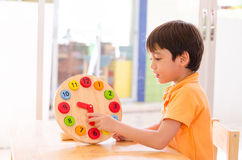 Tiempo de aprendizaje del niño pequeño con el juguete del reloj del educationa del montessori Imagenes de archivo